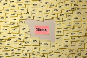 "One post-it note labeled ""Original"" surrounded by post-it notes labeled ""Copy."""