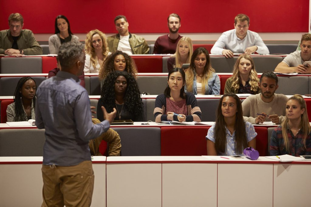 Back view of man presenting to students at a lecture theatre.
