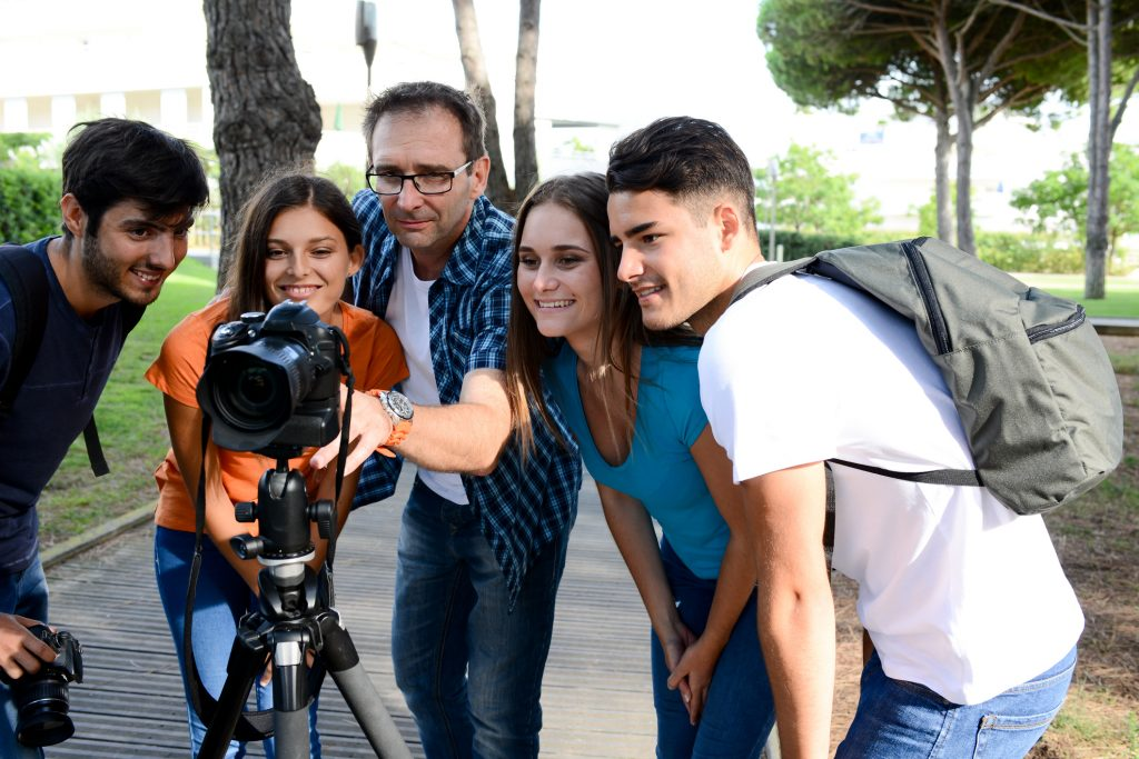Instructor showing students how to use a camera outdoors